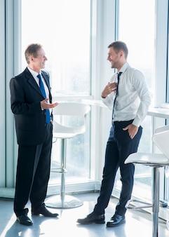 オフィスで会話をしているウィンドウの近くに立っている2つの笑顔のビジネスマン
