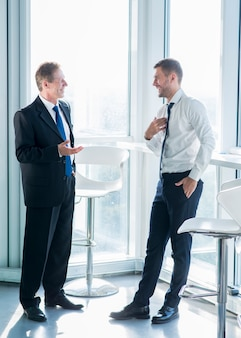 Two smiling businessmen standing near window having conversation in office