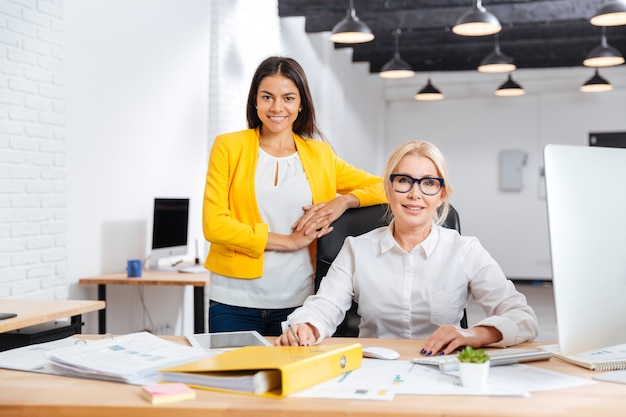 Две улыбающиеся женщины-предприниматели, работающие вместе над компьютером за столом в офисе и смотрящие в камеру