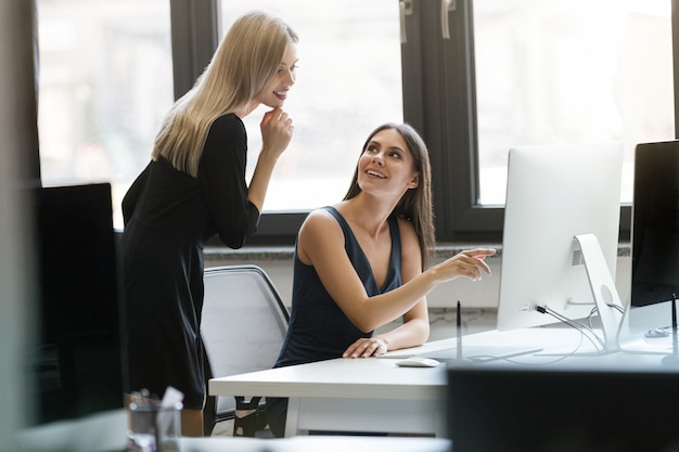 Two smiling businesswomen working with computer together