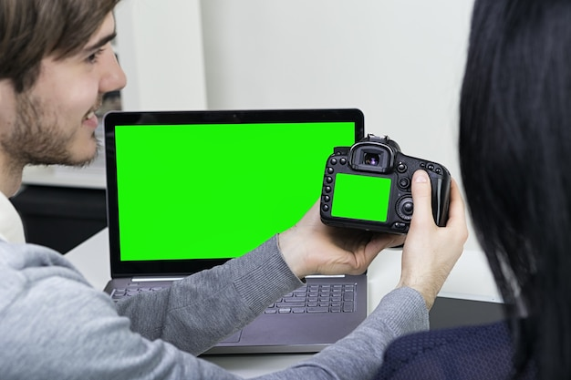 두 명의 웃는 캐주얼 디자이너 남성과 여성이 사무실에서 노트북과 태블릿을 가지고 일하고 있습니다. 그린 스크린 노트북 및 태블릿