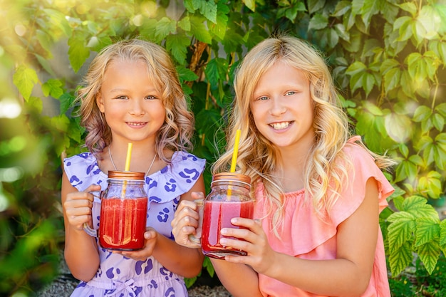 수박 스무디 항아리를 들고 두 웃는 백인 여자. 건강한 여름 음식 개념입니다.