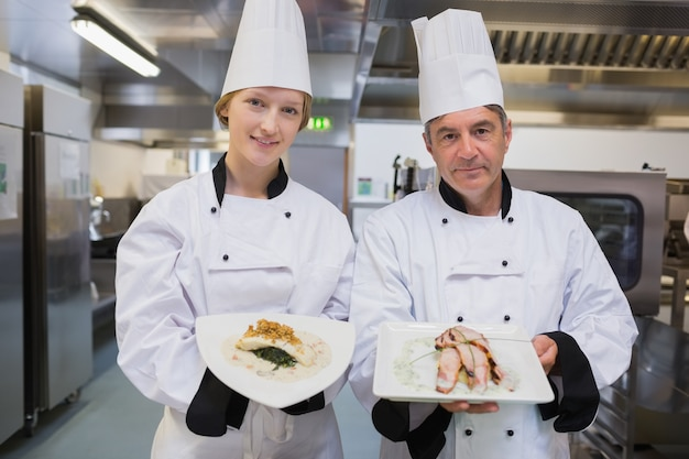 Two smiling chef's showing their dishes