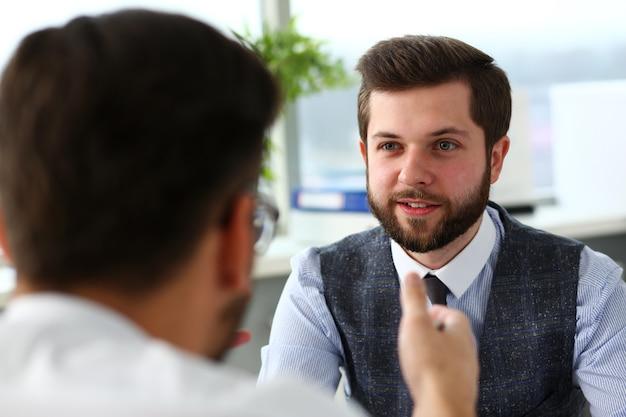 Два улыбающихся клерка-бизнесменов обсуждают проблему в офисе