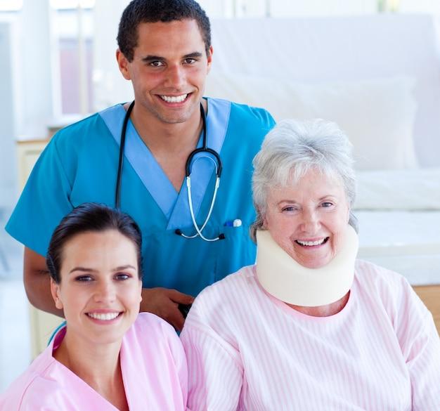 Два улыбающихся врача, которые заботятся о раненых старшей женщине