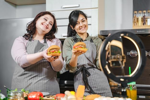 Две улыбающиеся женщины-блоггеры готовят гамбургеры и записывают видео на смартфон для социальных сетей или блога на кухне.