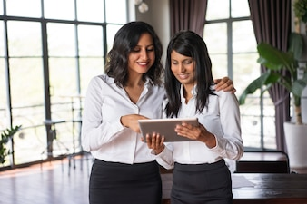 Two smiling female colleagues using tablet pc in cafe.