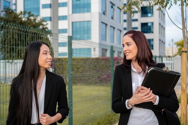 Две улыбающиеся женщины-коллеги приятно беседуют на территории компании