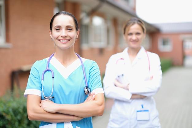 두 명의 웃는 여성 의사가 팔짱을 끼고 서 있다