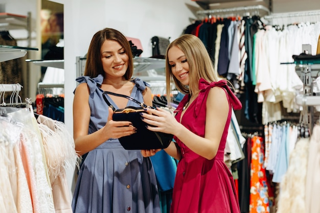 Two smiling female friends choosing choose a black bag in the store.