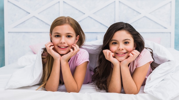 Two smiling female friends lying under the bed sheet looking to camera