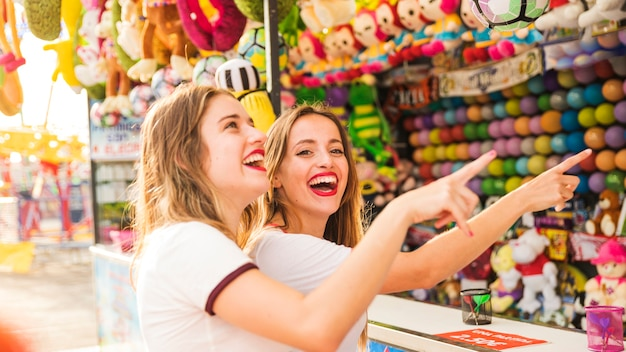 Two smiling female friends pointing finger at amusement park