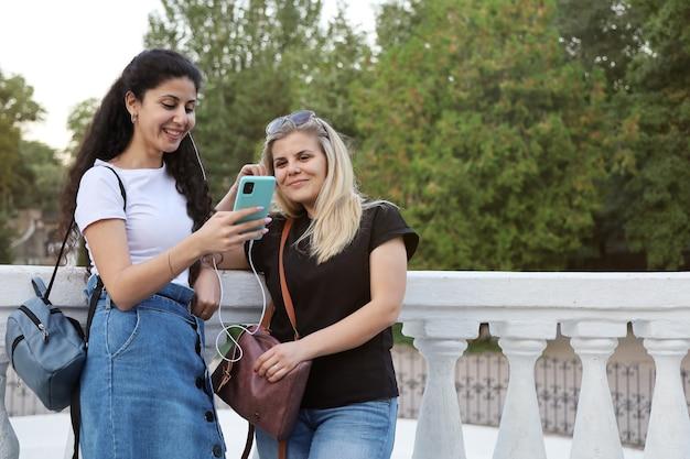 2人の笑顔の女性の友人が公園に立って、スマートフォンから同じヘッドフォンで聞いています