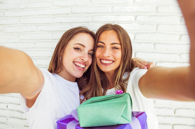 Two smiling female friends with birthday gift in front of brick wall