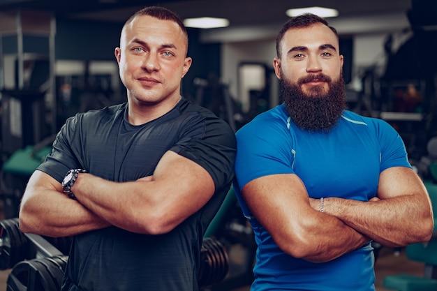Два улыбающихся мужчины-культуриста, стоящие бок о бок в тренажерном зале