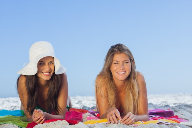 Two smiling friends lying on the sand
