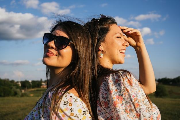 屋外で背中合わせに草の上に座っている2人の笑顔の友人。