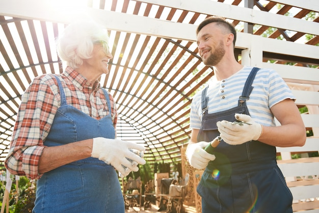Two smiling gardeners in sunlight