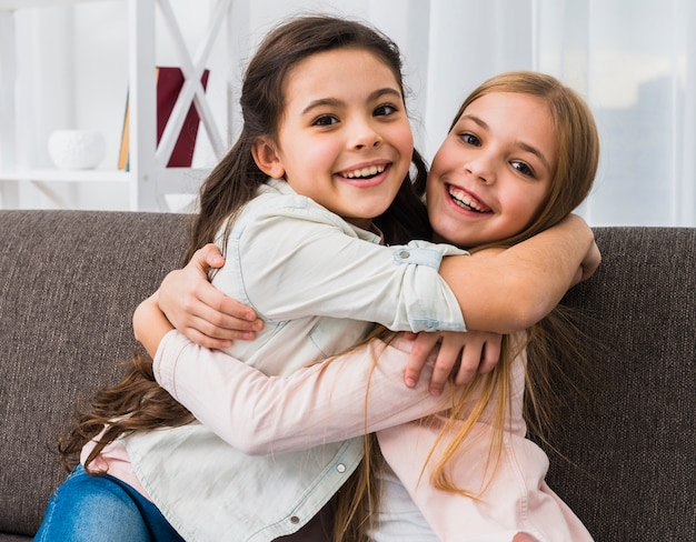 Two smiling girl embracing each other looking to camera at home