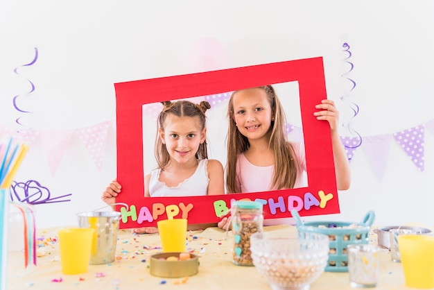 Two smiling girl holding happy birthday photo frame with different foods on table