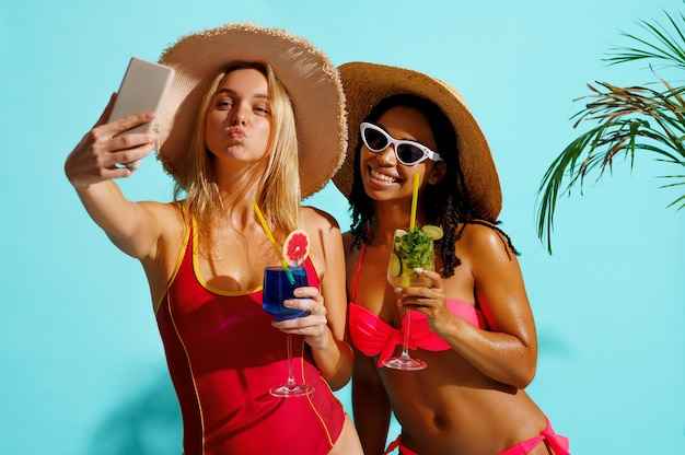 수영복에 웃는 두 여자 친구가 파란색에 셀카를 만든다.