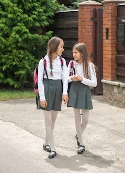 제복을 입은 두 명의 웃는 소녀가 학교에 걸어가 수다를 떨고 있다