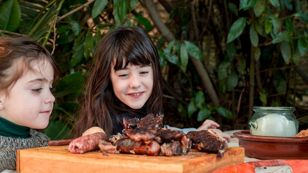 Two smiling girls looking at grilled meat on chopping board