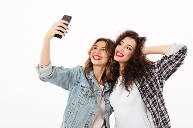 Two smiling girls posing together and making selfie on smartphone over white wall