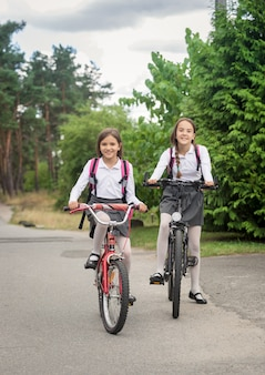 Two smiling girls riding bicycles to school