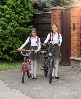 Two smiling girls in school uniform with bicycles in front of house