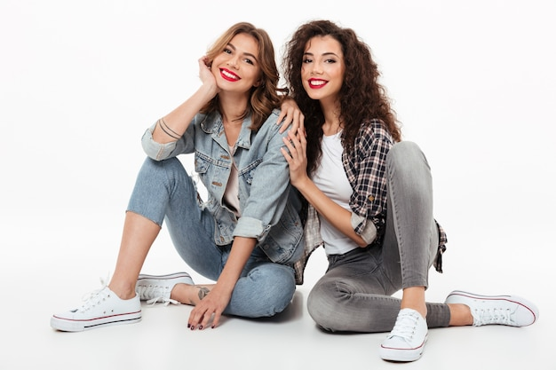 Two smiling girls sitting on the floor together  over white wall