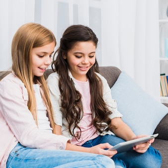Two smiling girls sitting on sofa looking at digital tablet