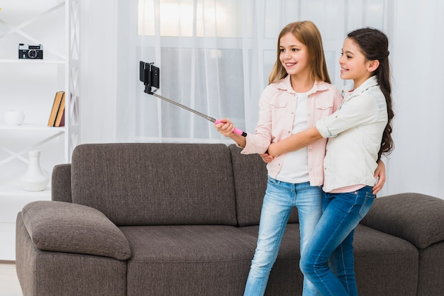 Two smiling girls standing in front of sofa taking selfie on smartphone