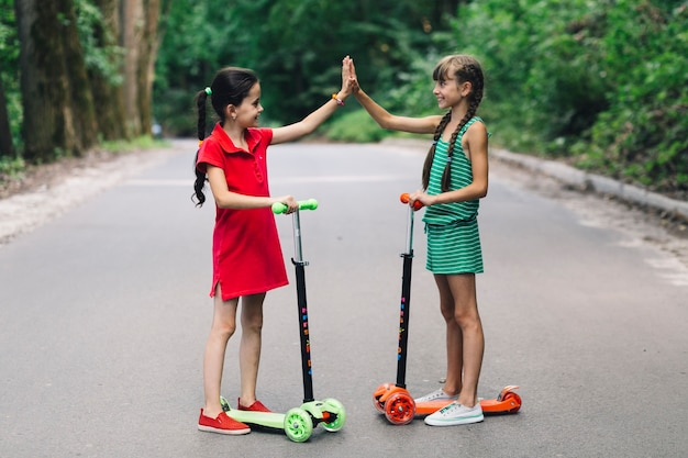 Two smiling girls standing on scooter giving high five gesture on road