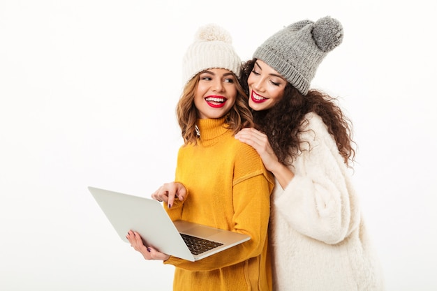 Two smiling girls in sweaters and hats standing together while using laptop computer over white wall