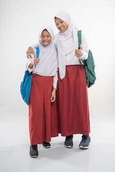 엄지 손가락과 학교 가방으로 후드 초등학교 교복을 입고 두 웃는 소녀
