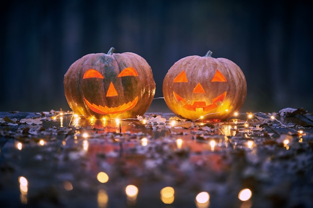 Two smiling halloween pumpkins on a wooden table with lights in a mystic forest at night