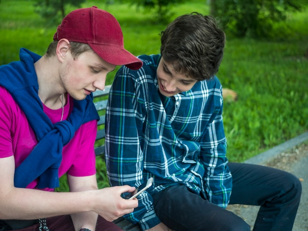 Two smiling handsome brothers checking photo on the mobile phone sitting on the bench