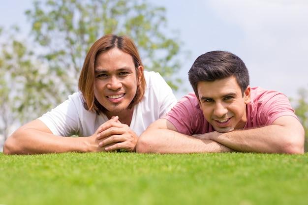 草の上に横たわる2人の笑顔のハンサムな男性