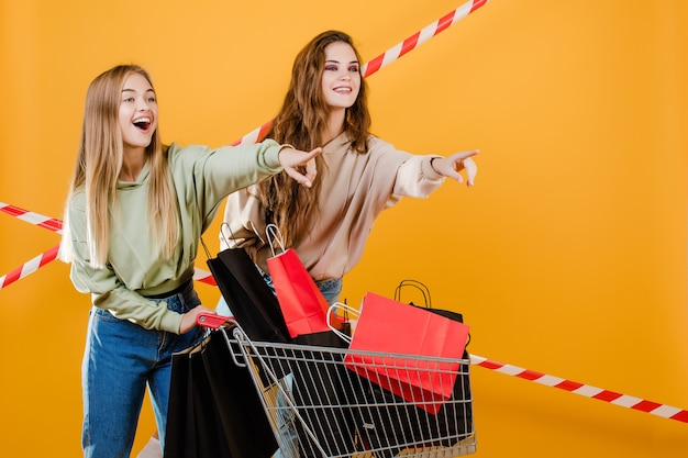 Two smiling happy beautiful women  with trolley pointing fingers at copyspace with colorful shopping bags and signal tape isolated over yellow