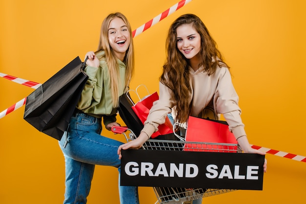 Two smiling happy girls with trolley have grand sale sign with colorful shopping bags and signal tape isolated over yellow