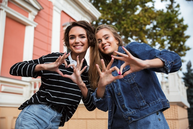 Two smiling happy teenage girls showing love gesture