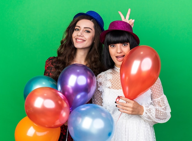 Two smiling and impressed young party girls wearing party hat both holding balloons  one making bunny ears behind her friend's head isolated on green wall