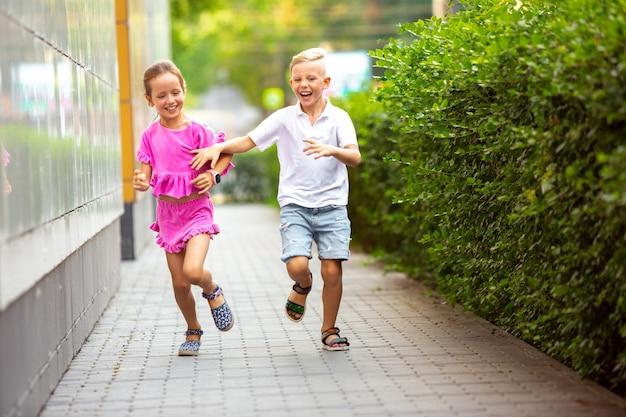 Два улыбающихся ребенка, мальчик и девочка вместе бегают по городу, городу в летний день