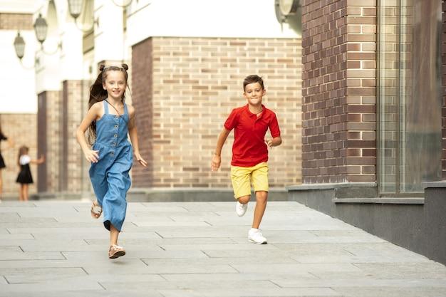 여름날 도시에서 함께 달리는 두 명의 웃는 아이 소년과 소녀