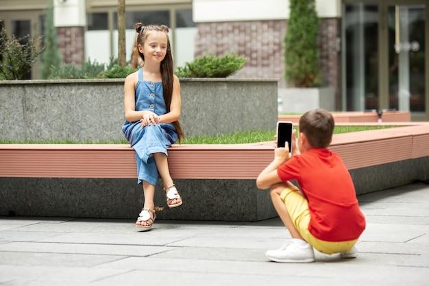 夏の日に町、街で一緒に写真を撮る2人の笑顔の子供、男の子と女の子