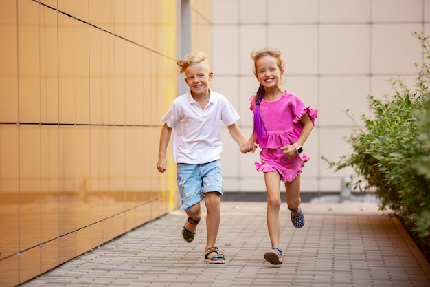Two smiling kids boy and girl running together in town city in summer day