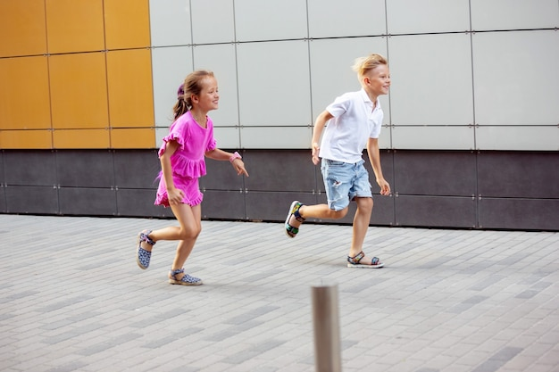 Two smiling kids, boy and girl running together in town, city in sunny day. concept of childhood, happiness, sincere emotions, carefree lifestyle. little caucasian models in bright clothes.