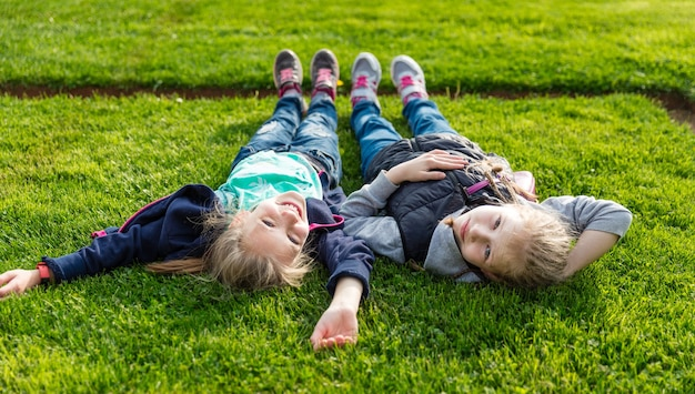 Двое улыбающихся детей, лежа на траве.