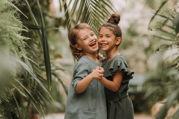 手をつないで歩いているリネンの服を着て異なる人種に属する2人の笑顔の少女